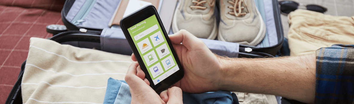 man packing for holiday with his mobile phone app