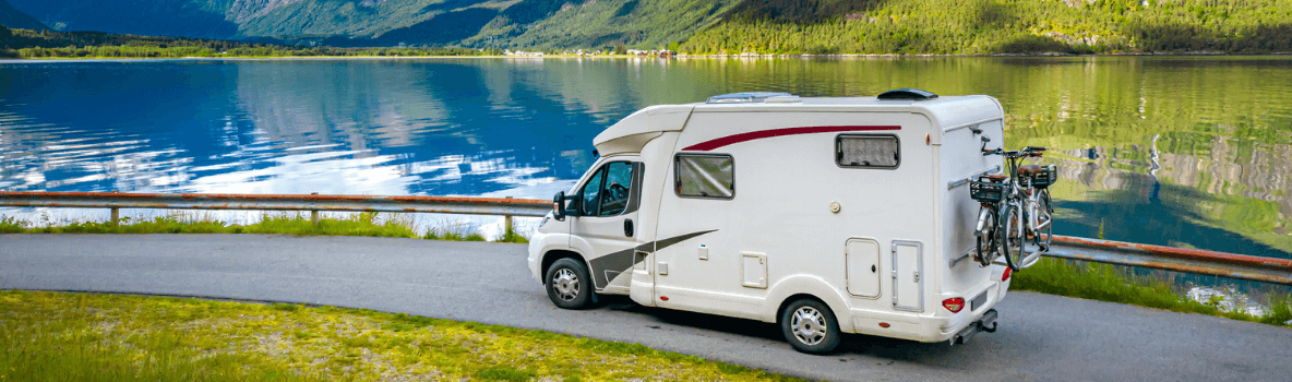 motorhome driving next to a lake